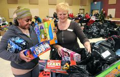 Farah Lahens (left), a Calvary Pentecostal Assembly church volunteer, and Bonnie Dion (right), fund development co-ordinator for the Cambridge Self-Help Food Bank, fill one of the many bags with toys for people in need.