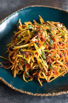 Light and bright shredded carrot salad with chopped toasted walnuts, currants, and a walnut oil curry vinaigrette. Super quick and tasty.