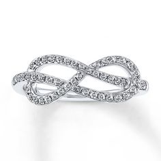 Swirling from either side toward the center, a row of brilliant round diamonds traces an infinity symbol in this romantic ring for her. Crafted of 10K white gold, the ring has a total diamond weight of 1/3 carat. Diamond Total Carat Weight may range from .29 - .36 carats.