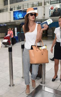 Alessandra Ambrosio looked jet-setter chic but stayed totally comfy in a slouchy white tank, striped chino boyfriend pants by Big Star, and suede espadrilles. The seasoned traveler prepared for a sunny destination with a woven hat and glam shades.