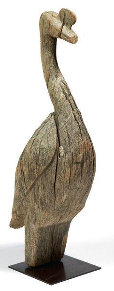 SCULPTURE funéraire en bois raviné représentant un oiseau (sans doute un échassier) dont le bec est orné d'un petit pédoncule. Aire Sakalava ou Vézo. Madagascar.