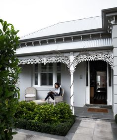 Georgina Austin relaxes with a book on the front verandah of her double-fronted brick Victorian home in Prahran, Melbourne.