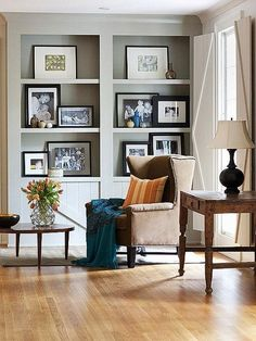 Take a cue from this simple yet stylish sitting room and fill shelves with framed family photographs in black and white in a gallery style. Couple them with a few small sculptural objects and favorite artwork.