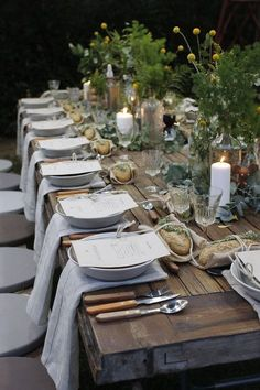 Beautiful table setting - using bottles as vases with flowers or greenery, candles, neutral napkins, bread on burlap