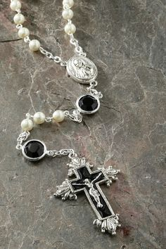"The sophisication and simplicity of black and white. This rosary features a black enameled cross and ½"" Jet Swarovski® crystals combined with pearls. Let this rosary help you meditate on the price tha"