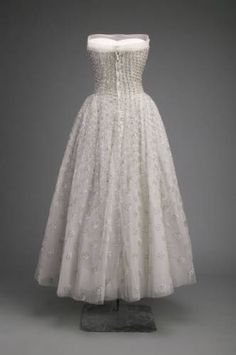 Christian Dior Couture evening gown circa 1953. Made from light pink silk tulle beaded with silver-colored sequin and rhinestone trim. Fitted strapless design with bell shaped bouffant skirt composed of several layers of tulle to create volume and attached to a understructure girdle to provides the shape of the skirt, cinching the waist and torso while providing support for the breasts. The wearer simply stepped into the gown to be ready for the evening. #Christian #Dior # House of Dior. France.
