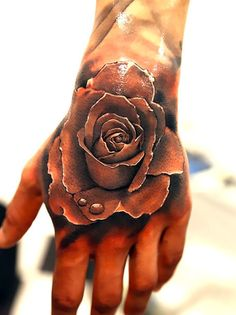 Beautiful tattoo of rose with drop of water on the hand. 3D effect makes it very realistic