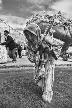 Una mujer porteadora se dirige hacia la frontera entre Marruecos y España con un pesado bulto a la espalda. Tras ella, algunos hombres hacen el mismo trayecto. Los pocos hombres que participan en este comercio irregular de mercancías no cargan bultos sobre la espalda. Se limitan a empujarlos y hacerlos rodar. La mayoría de mujeres tendrá que caminar hasta las naves del lejano polígono, cargar sobre sus lumbares y alcanzar la valla.