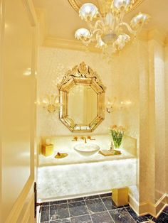 The Venetian-inspired powder room features under-lit white onyx marble countertop with apron front. The dome space was created to accommodate the beautiful Murano glass chandelier. Matching sconces highlight ornate Venetian mirror as it perfectly finishes the space.
