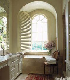 In this master bath designed by Fern Santini, Princess Yellow limestone from Ann Sacks surrounds a bathtub by Kohler.