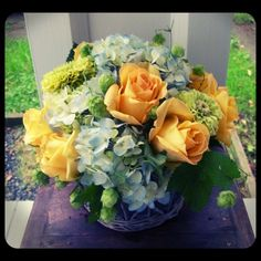 Rustic basket filled with blude hydrangea, yellow roses, chartreuse zinnias and fresh hops.  Roberts Flowers of Hanover, Hanover, NH