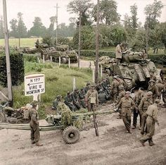 British Sherman tanks and 6-pdr anti-tank guns of the 11th Armoured Division, advancing through the village of St Charles-de-Percy in Calvados, Normandy, on the N 177 road to Vire. 2nd of August 1944,  (Source – © IWM B 8488 – Sgt. Laing – No 5 Army Film & Photographic Unit)  (Colourised by Allan White from Australia)