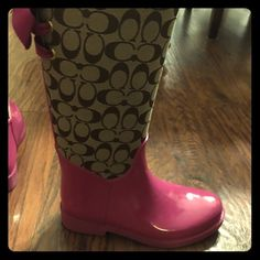 Coach Tristee signature rainboot These lace up the back and add some sass to a rainy day! They ups are adjustable to your calf size! Super soft and comfortable on the inside. They are lined in an acrylic like lining for added comfort and warmth. In fair condition. I literally only wore these 5 times, but my dog chewed the pink piping off of the top of the boot (as seen in pics). This could be hot glued. Price reflects dog destruction.  Coach Shoes Lace Up Boots