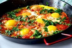 Traditional shakshuka - Israeli breakfast with eggs, sweet peppers, onions, garlic, tomatoes and herbs. A simple and healthy authentic recipe.