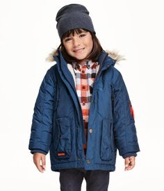 Padded parka in woven fabric with detachable, pile-lined hood with faux fur trim. Zip and wind flap at front with snap fasteners, chest pockets, and front pockets with flap and fastener. Ribbing at cuffs and neck. Lined partly in pile.