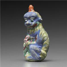 AN ENAMELED BUDDHIST-LION-FORM PORCELAIN BOTTLE