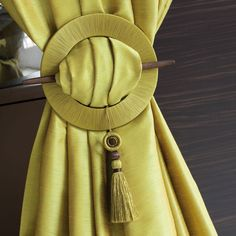 Use a grommet, cover with fabric and secure using a decorative element. A unique tieback that is sure to impress. #trendytiebacks