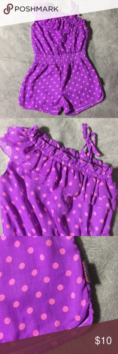 Toddler Girl Shirts Romper Size 4 Super Cute Toddler Girl shorts romper. Size:4 Color: purple with pink polka dots. Material: 100% poly. Ruffle asymmetrical top with tie side ribbon closure. Elastic at waistband. Great Condition. Tag says 4 fits more like a 4T. Dollhouse Bottoms Jumpsuits & Rompers