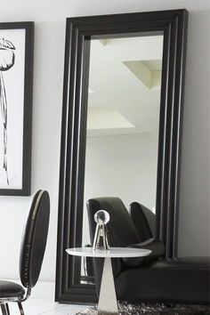 Mirrors come in all shapes and sizes and serve different functions. A large leaning mirror can be used to help open up a small, enclosed room or can be set behind an ornate side table to create a decorative seating arrangement with two upholstered chairs on each side. | Catania Mirror cort.com