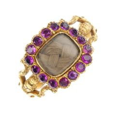 A gem-set mourning ring, the rectangular woven hair panel, within a circular-shape foil-backed ruby surround, to the scrolling shoulders. Weight 3.5gms.
