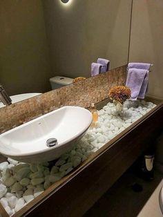 A cuba para banheiro combina perfeitamente com as pedras que decoram a bancada de vidro e madeira