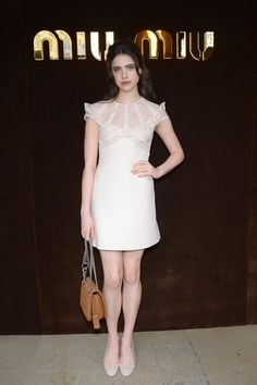 Margaret Qualley wears a lace mini dress with a chain-strap bag and neutral heels