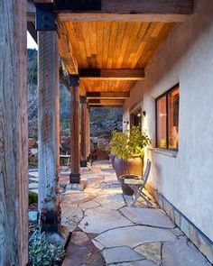 Straw Bale home with lovely flagstone patio - love these heavy post & beams, and the combination of chunky natural materials in this contemporary, rustic style.