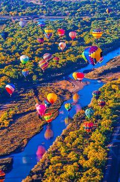Hot air balloons flying low over the Rio Grande River just after sunrise, Albuquerque International Balloon Fiesta, Albuquerque, New Mexico, USA.