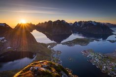 Panoramic view above Reine on the Lofoten Islands (Norway). The sun is about to set behing the distant peaks.
