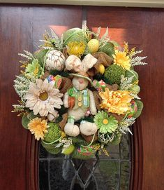 This 24 inch burlap and deluxe mesh wreath has a cute fleecy bunny in the center with lots of colorful flowers, decorative wooden balls, Easter eggs and flower picks with decorative ribbon and roping all through the wreath.