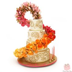 The highlight of the cake is the ombré floral cascade that transitions from a light pink to fuchsia to coral and finally to yellow. Additional gold piped henna designs along with a gold rope decorated each tier.