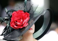 Kentucky Oaks fan sports a hat featuring a large red rose as she takes in the action at Churchill Downs in Louisville, Kentucky, on the day before the Kentucky Derby on May 4, 2012.