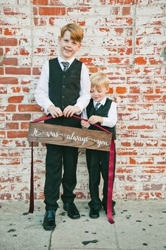 Adorable ring bearers + sign: Photography : One Love Photography | Photography : onelove photography Read More on SMP: http://www.stylemepretty.com/california-weddings/los-angeles/2016/07/18/youll-love-how-this-bride-surprised-her-groom-at-their-destination-wedding/