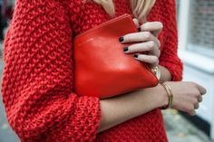red sweater red clutch