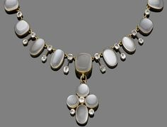 A late 19th century moonstone and paste pendant necklace  The fringe necklace designed as a graduated row of collet-set oval and cushion cabochon moonstones, alternating with circular-cut paste, suspending a detachable circular and oval cabochon moonstone cross with paste highlights, mounted in 18 carat yellow gold, partial UK hallmark, lengths: pendant 4.5cm, necklace 4.5cm
