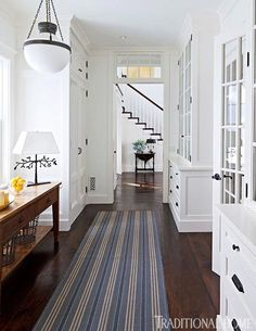 A spacious hallway behind the dining room is lined with  cabinets and doubles as a butler's pantry. Warming the dark hardwood floors is  a blue and white rug runner from Patterson, Flynn & Martin.