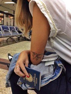 Tatuagem de mapa mundi nos braços de uma mulher sentada no aeroporto.