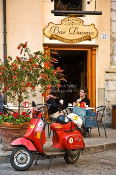 Couple eats breakfast at outdoor table, their red Vespa motorscooter parked at curb in front of the The Bar Duomo, Pasticceria and Gelateria, Piazza Duomo, Cefalu, Sicily, Italy  Copyright:© 2007 Chuck Pefley