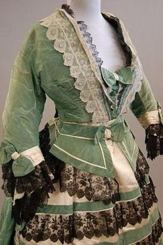 A green watered silk formal gown, circa 1865, the  Sign In to see what this sold for  A green watered silk formal gown, circa 1865, the lightly padded bodice trimmed with cream and black lace and bows, the horizontally banded skirt with matching waist-sash, (3)      Condition report  Skirt is very badly stained to front left side of hem, brown damp speckles over the shoulders of the bodice,2 buttons missing from bodice by xiaoxuanluo