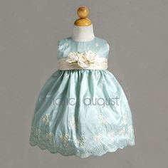 Mint Easter Baby Dress with a Sprinkle of Flowers: Starting from the classic, sleeveless bodice, dainty little embroidered ivory flowers that cascade down the length of the beautiful mint green taffeta dress and floating along the beautiful, scalloped hem. The skirt holds a gentle volume well, making this a Easter dress that is charming, classy, and oh-so cute! Lastly, a complimenting ivory sash adorns the waist with a trio of detachable soft rose pins.