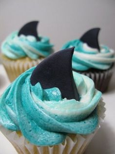 Cupcakes are a great dessert option. You can use any cupcake recipe you wish to make the cupcakes pictured. Use white icing and some blue food coloring, and get some fondant or gray paper cut into triangles for fins. Cupcakes Design, Cupcakes Au Cholocat, Shark Cupcakes, Yummy Cupcakes, Birthday Cupcakes, Beach Themed Cupcakes, Swimming Cupcakes, Ocean Cupcakes, Mermaid Cupcakes