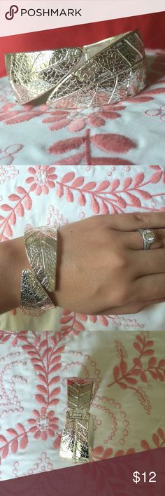 "Silver tone Leaf hinge bangle Gorgeous bracelet with a silver tone leaf design. Adds a touch of shine to your outfit while still being neutral. Hinge closure. Measures 2.5"" across. Like new condition. Bundle for a discount. Jewelry Bracelets"
