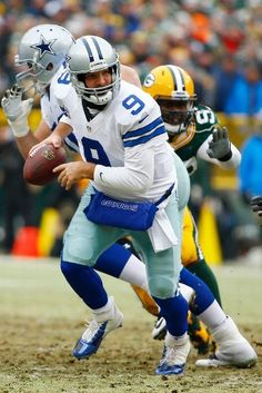 Dallas Cowboys vs. Green Bay Packers - Quarterback Tony Romo #9 of the Dallas Cowboys looks to hand off the football against the Green Bay Packers in the first quarter of the 2015 NFC Divisional Playoff game at Lambeau Field on January 11, 2015 in Green Bay, Wisconsin. (Photo by Al Bello/Getty Images)