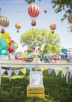 A Hot Air Balloon Birthday Party with vintage travel decor, pilot's helmet, DIY first year photo display, hot air balloon cake + cloud & balloon cookie pops