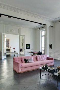 Das Highlight dieses schlichten Wohnzimmers in Weiß und Grau? Ein rosanes Sofa passend zum Stil des Altbaus!