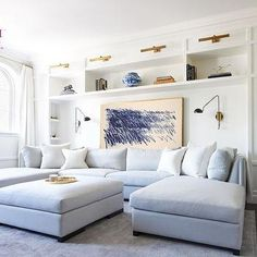 Chic Living Room Features A Wall Of Built In Shelves Illuminated By Br Picture Lights Lined With Gray Blue Sectional Two Chaise Lounges