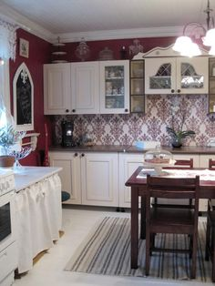 Country kitchen: wooden kitchen cabinets I designed, backsplash is Finnish printed wallpaper and on top a plexiglass for easy wiping.