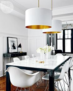 Dining Room Light - In the dining room, wainscotting and herringbone floors are juxtaposed with a clean-lined marble and clear-lacquered raw steel table surrounded by iconic Mid-Century Modern Eames chairs. The white linen drum pendant lights, lined in a brass colour, add drama.