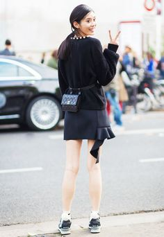 Black mini skirt accessorized with a Chanel fanny pack and black sneakers