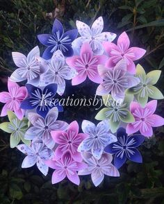 These beautiful Pink and Purple and Green Origami Flower Wreath would be a stand out on your front door!! These could be used as centerpieces, candle decor or used as party decor. This would also be a perfect gift to welcome a new baby. The possibilities are endless!    The wreath is made from specialty scrapbook paper that are cut into 3x3 then folded into a petal to be combined to make a beautiful flower. The span of the flower is approx 3. They are hand glued to a base and the base is…